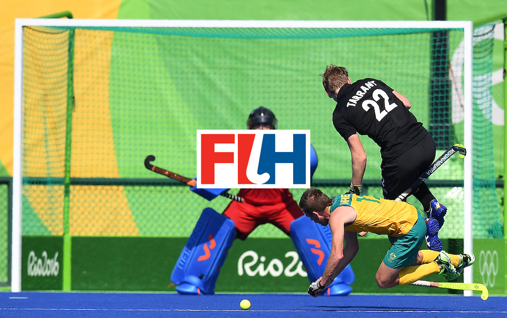 New Zealand's goalkeeper Devon Manchester watches as Australia's Jake Whetton (C) tries to score a goal and New Zealand's Blair Tarrant jumps during the men's field hockey Australia vs New Zealand match of the Rio 2016 Olympics Games at the Olympic Hockey Centre in Rio de Janeiro on August, 6 2016. / AFP / MANAN VATSYAYANA        (Photo credit should read MANAN VATSYAYANA/AFP/Getty Images)