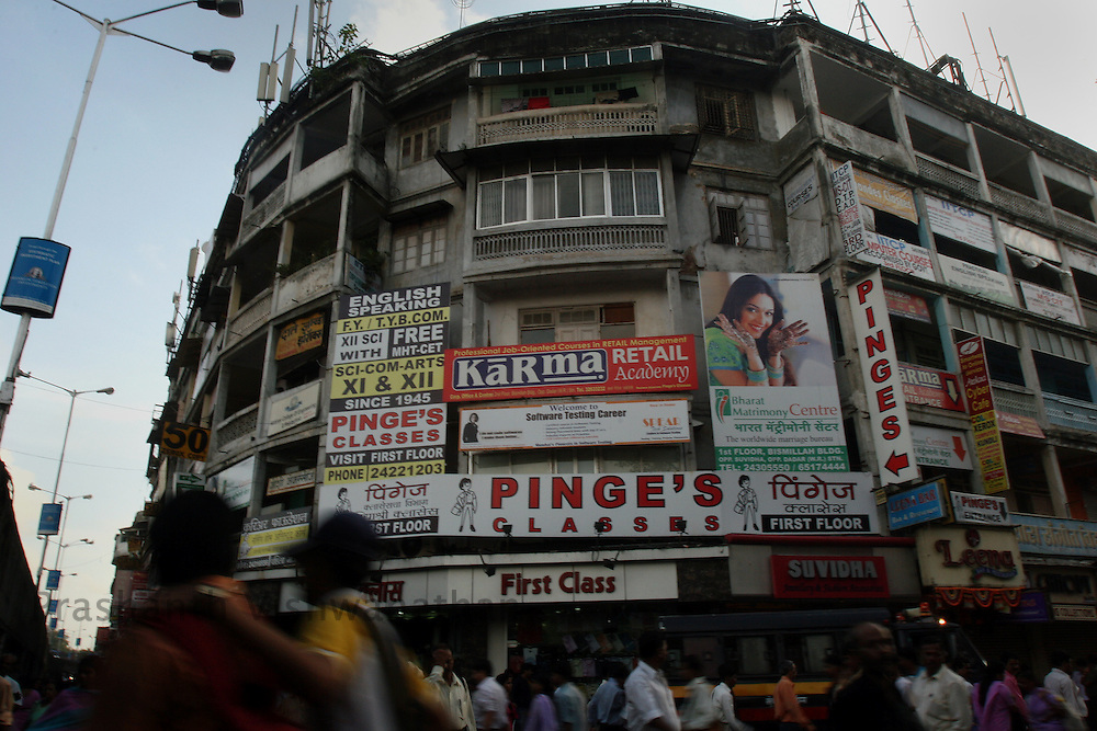 People walk past a building housing many of the English Speaking Classes adjacent to the Dadar station, in Mumbai, India, on Monday August 20, 2007. Photographer:  Prashanth Vishwanathan