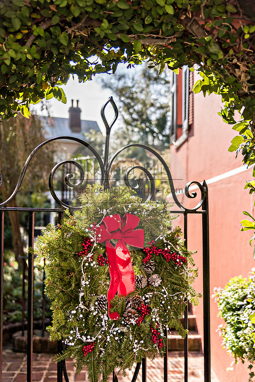 A wrought iron garden gate of a historic home decorated with a Christmas wreath on Water Street in Charleston, SC.