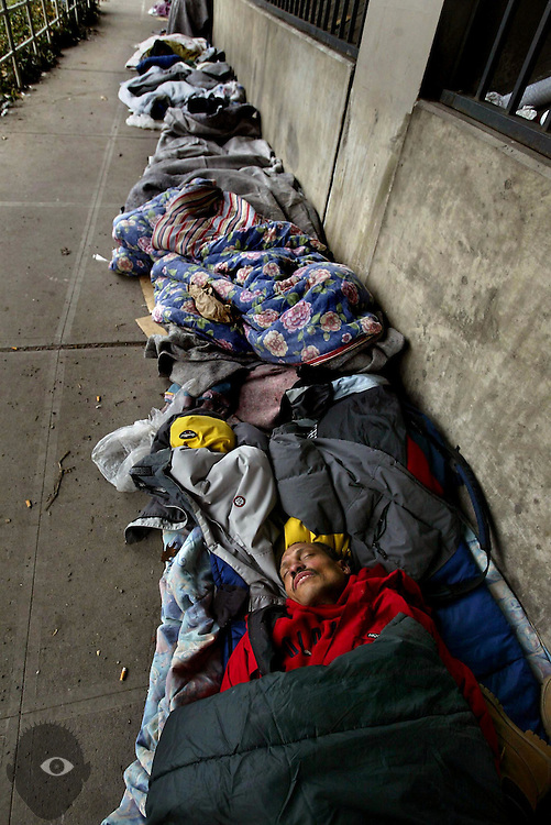 January 04, 2004  --  A line of homeless people attempt to stay warm on a very cold day while camped out along Fron Street near the Steel Bridge....KEYWORDS: snow, weather