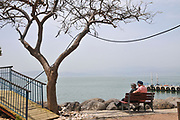Mature couple sits together in front of the Sea of Galilee