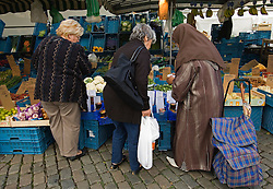 ANTWERP, BELGIUM - OCT-7-2006 - Muslims mix easily with the local population at an outdoor market in Antwerp's city center. Immigrants in Belgium and especially those of Arab decent, have come under attack from the Flemish extreme right political party, the Vlaams Belang, which espouses an anti-immigration policy and is trying to capitalize on the clash between Islamic and European values. (Photo © Jock Fistick)