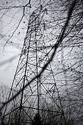 The dark outline of an electricity pylon stands over a gloomy winter sky in woodland near Wrington, North Somerset England.