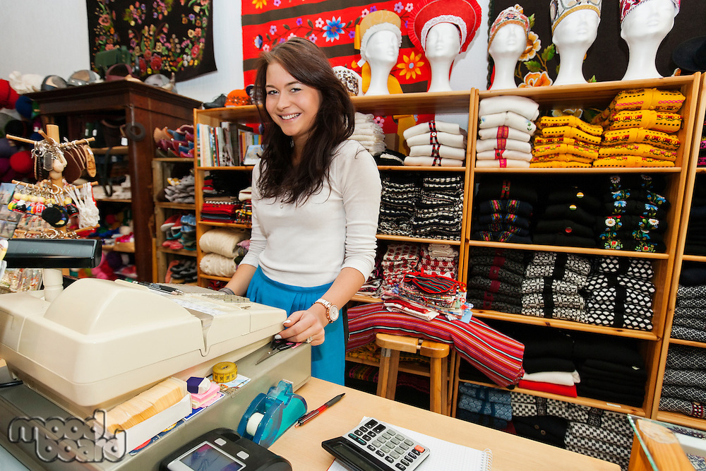 Portrait of smiling young female salesperson at checkout stand in gift store
