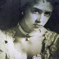 A monochromatic portrait of a woman in a heavily embroidered white/bridal gown, with pearl necklace and a head dress.