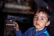 Portrait of a child at the local blacksmith located within the Roma area in Frumusani.
