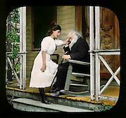 """The Image of Her"" a pretty young woman with an elderly bearded man in a rocker on his porch. Vintage photo circa 1910."