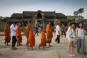 Young boy Buddhist monks walk past tourists through the ancient ruins of Angkor Wat temple grounds Siem Reap, Cambodia. Angkor Wat is one of UNESCO's world heritage sites. It was built in the 12th century initially as a Hindu temple which then transformed into a Buddhist temple by the end of the 12th century. (photo by Andrew Aitchison / In pictures via Getty Images)