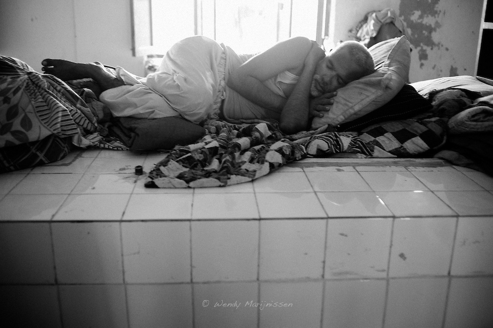 A man sleeps on a counter of a physics lab in a college that now houses displaced people affected by the floods. Karachi, Pakistan, 2010