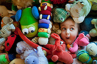 young girl hides in a pile of stuffed animals with only her face emerging.