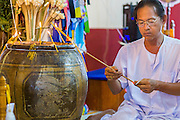 29 JUNE 2014 - DAN SAI, LOEI, THAILAND:  A man lights a candle during a ceremony in Wat Ponchai on the last morning of the Ghost Festival. Phi Ta Khon (also spelled Pee Ta Khon) is the Ghost Festival. Over three days, the town's residents invite protection from Phra U-pakut, the spirit that lives in the Mun River, which runs through Dan Sai. People in the town and surrounding villages wear costumes made of patchwork and ornate masks and are thought be ghosts who were awoken from the dead when Vessantra Jataka (one of the Buddhas) came out of the forest. On the last day of the festival people participate in merit making ceremonies at the Wat Ponchai in Dan Sai and lead processions through town soliciting donations for the temple.   PHOTO BY JACK KURTZ