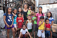 UK celebrity Myleene Klass poses for a photograph with slum children in an urban slum in Paranaque City, Metro Manila, The Philippines on 18 January 2013. Photo by Suzanne Lee for Save the Children UK