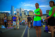 21 JULY 2012 - MINNEAPOLIS, MN:  People walk across the Stone Arch Bridge in Minneapolis, MN. The Stone Arch Bridge is a former railroad bridge crossing the Mississippi River at Saint Anthony Falls in downtown Minneapolis, Minnesota. Positioned between the 3rd Avenue Bridge and the I-35W Saint Anthony Falls Bridge,[2] the Stone Arch Bridge was built in 1883 by railroad tycoon James J. Hill for his Great Northern Railway, and accessed the former passenger station located about a mile to the west, on the west bank of the river. The structure is now used as a pedestrian and bicycle bridge. It is an Historic Civil Engineering Landmark, and was added to the National Register of Historic Places in 1971 as a part of the Saint Anthony Falls Historic District.   PHOTO BY JACK KURTZ