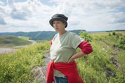 """Marilyn Mullens poses next to a mine on Kayford Mountain in southern West Virginia. She organized the Memorial Day protest against mountaintop-removal mining: """"We just want people to be aware. Know that every time you turn on a light switch . . . someone here is paying for that with dirty water, with air that they can't breathe."""" Mountaintop Removal is a method of surface mining that literally removes the tops of mountains to get to the coal seams beneath. It is the most profitable mining technique available because it is performed quickly, cheaply and comes with hefty economic benefits for the mining companies, most of which are located out of state. © Ami Vitale"""