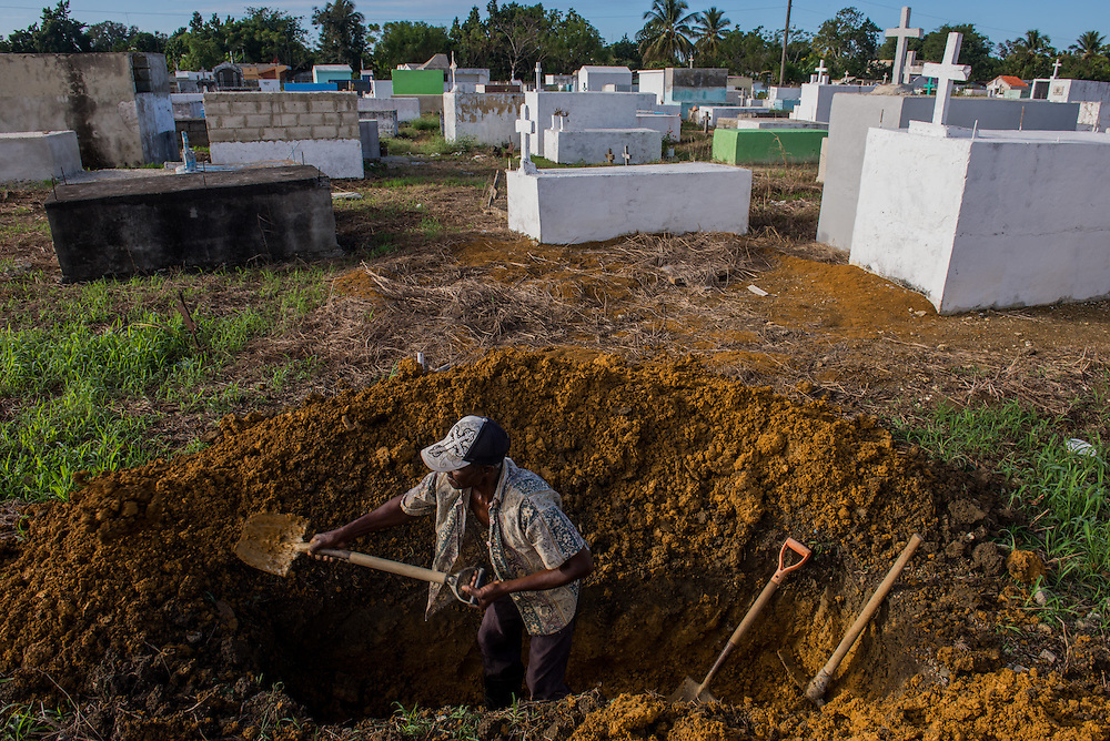 A Haitian man digs a grave in the Consuelo cemetery, Jan. 12, 2014. Haitians typically can not afford coffins and traditional Dominican grave sites so are often buried en masse on the peripheries of the cemetery, segregated from Dominicans even in death.