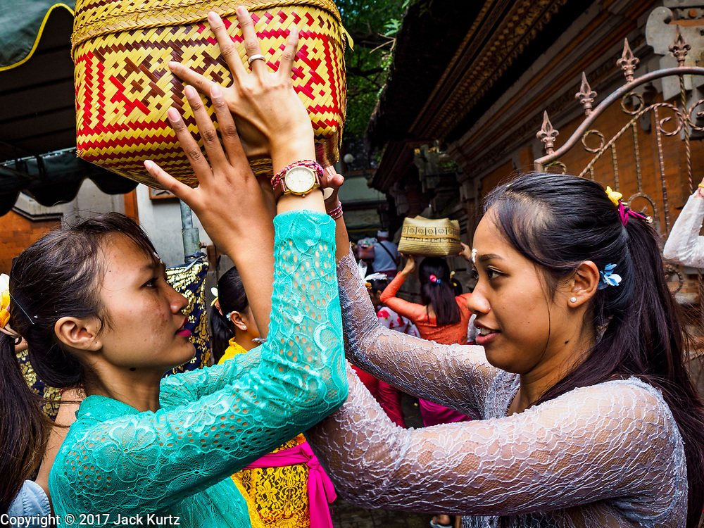 "02 AUGUST 2017 - UBUD, BALI, INDONESIA: Women get their baskets of offerings ready to take into the temple during the ""Merchants' Day"" ceremony at the Pura (Temple) Melanting Pasar Ubud, the small Hindu temple in the Ubud market. It's a day that merchants throughout Ubud come to the temple to make offerings and pray for prosperity.    PHOTO BY JACK KURTZ"