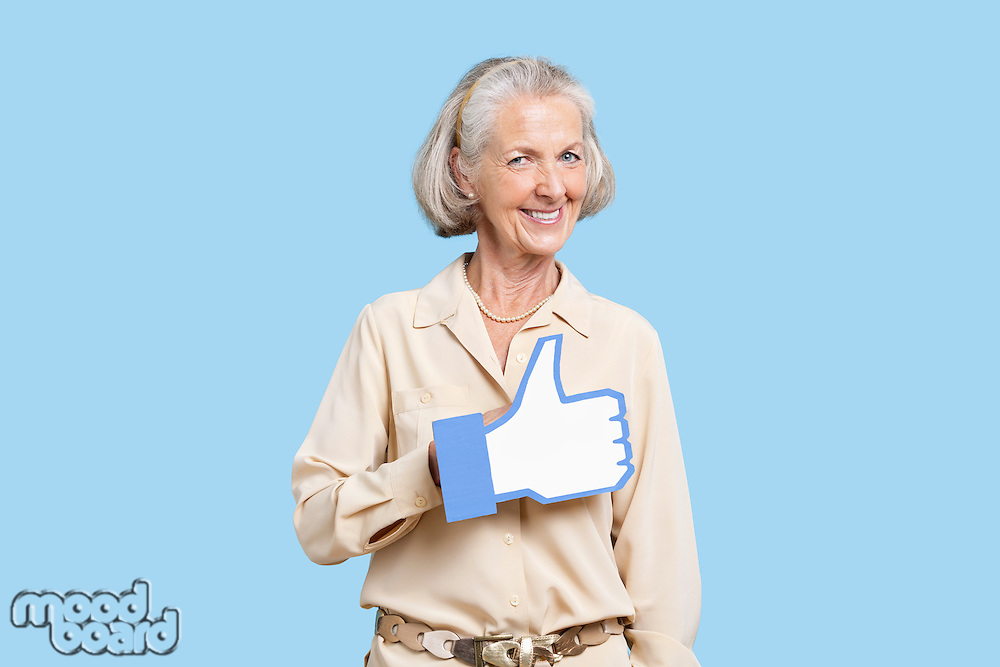 Portrait of senior woman in casuals holding fake like button against blue background