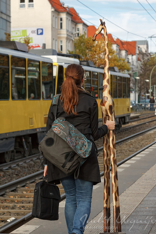 A woman carries a wooden giraffe on a Berlin street