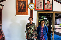 A portrait of Mr. Kawai Thanthongdee and his wife Laor, with images of the royal family and a praying monk, in front of their small home in Sakon Nakhon, northeastern Thailand.