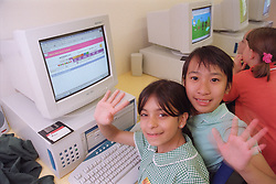 Primary school girls sitting in front of computer waving during Information and Technology lesson,