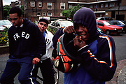 Group of teenage boys two on a bicycle one with a motorbike helmet Lambeth Walk South London c.2000