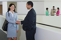 Business people shaking hands in office hallway