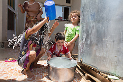 © Licensed to London News Pictures. Hamdaniyah, Iraq. 26/07/2014. Dilar Minowar Salim, 9, pours water over her head after being resupplied with fresh drinking water by Kurdish Zeravani soldiers at the partially built home she shares with 16 other family members in Hamdaniyah, Iraq. Dilar and her family left Mosul on Friday the 18th of July when Islamic State fighters issued an ultimatum to the city's Christian community. When the family left they were forced to pay a tax for their car and the eldest son (19) was threatened at knifepoint to ensure they handed over all of their possessions including family photographs.<br /> <br /> Having taken over Mosul Iraq's second largest city in June 2014, fighter of the Islamic State (formerly known as ISIS) have systematically expelled the cities Christian population. Despite having been present in the city for more than 1600 years, Christians in the city were given just days to either convert to Islam, pay a tax for being Christian or leave; many of those that left were also robbed at gunpoint as they passed through Islamic State checkpoints.. Photo credit : Matt Cetti-Roberts/LNP