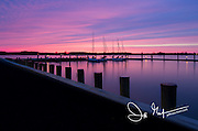 Beautiful pink and purple sky as the sun sets behind sailboats docked in Oxford, Maryland, part of the Eastern Shore.