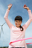 Girl (7-9) playing with hula hoop at wind farm, portrait