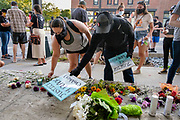 """20 AUGUST 2020 - DES MOINES, IOWA: People lay flowers and candles at an impromptu memorial for missing Black children. About 150 people, members of and supporters of Des Moines Black Liberation Movement (which used to be known as Black Lives Matter) marched through a residential neighborhood of Des Moines Thursday night demanding justice for Black children. The march was called to show support for Breasia Terrell and  Abdullahi """"Abdi"""" Sharif, two Black children who went missing in Iowa this year. Terrell, a 10 year old girl,  went missing on July 10 and is still missing. Sharif, a teenager, disappeared from a Des Moines shopping mall in January, his body was found in May. Members of BLM said authorities have not adequately investigated the disappearances.     PHOTO BY JACK KURTZ"""