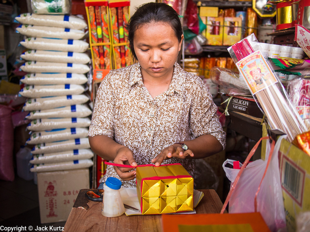 "26 AUGUST 2013 - BANGKOK, THAILAND: A woman makes boxes for Ghost Money to sell people celebrating Hungry Ghost Month at the Poh Teck Tung foundation temple in Bangkok. Poh Teck Tung operates hospitals and schools and provides assistance to the poor in Thailand. The seventh lunar month (August - September in 2013) is when the Chinese community believes that hell's gate will open to allow spirits to roam freely in the human world for a month. Many households and temples will hold prayer ceremonies throughout the month-long Hungry Ghost Festival (Phor Thor) to appease the spirits. During the festival, believers will also worship the Tai Su Yeah (King of Hades) in the form of paper effigies which will be ""sent back"" to hell after the effigies are burnt.     PHOTO BY JACK KURTZ"