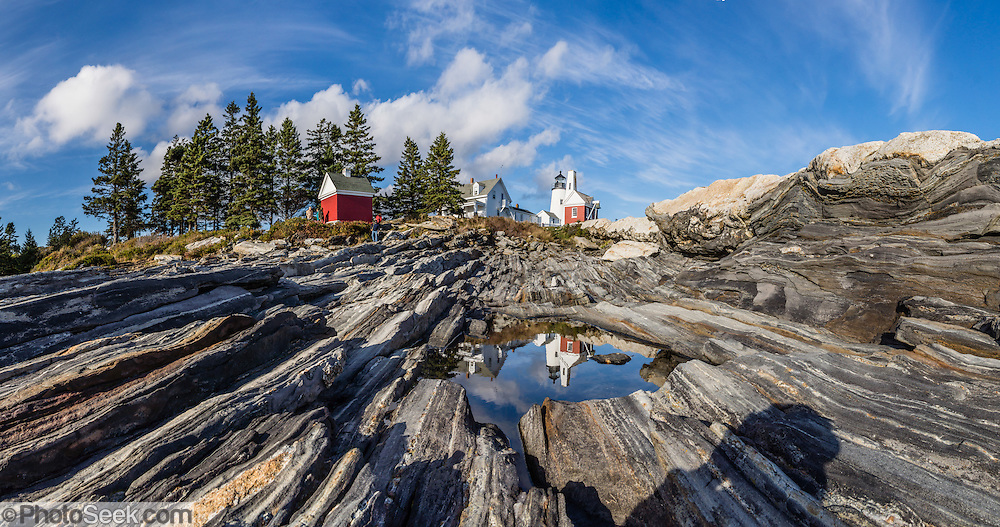 A unique landscape of beautifully striped bedrock descends from Pemaquid Light to the Atlantic Ocean. Pemaquid Point Lighthouse was built in 1835 and commemorated on Maine's state quarter (released 2003). Visit Lighthouse Park at the tip of Pemaquid Neck in New Harbor, near Bristol, Lincoln County, Maine, USA. From Damariscotta on bustling US Highway 1, drive 15 miles south on Maine Route 130 to the park. The keeper's house (built 1857) is now the Fishermen's Museum at Pemaquid. Geologic history: Silurian Period sediments laid down 430 million years ago were metamorphosed underground into a gneiss 360-415 million years ago, and intruded by molten rock which cooled slowly, creating the park's exposed metamorphic gray rocks with dikes of harder, white igneous rock. Underground heat and pressure tortured and folded the rock layers into the striking patterns that are now pounded and polished by the sea and rough weather. The panorama was stitched from 2 overlapping photos.