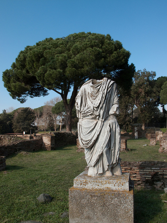 Ostia Antica. Headless statue, wearing a toga, along the street; umbrella pine tree behind it.