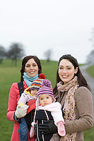 Two mothers with babies in baby carriers in park