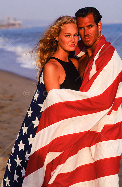 All American couple wrapped in an American Flag at the beach in Malibu, CA