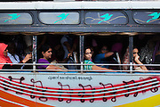 People traveling by a crowded local bus in Kollam, Kerala, India