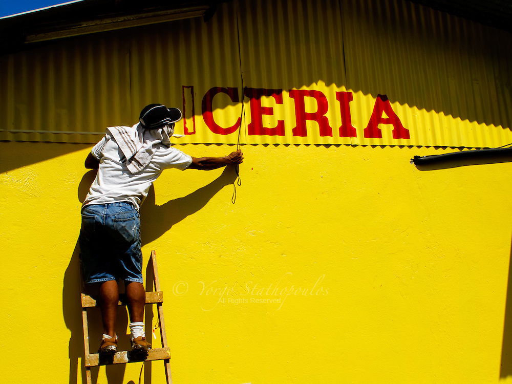 This Costa Rican is about to finish paining a sign for his new shop. It will spell C-A-R-N-I-C-E-R-I-A (butcher shop)