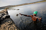 Extracting rock salt from the bed of Lake Katwe, Uganda, on Saturday, Dec. 29, 2007. Rock salt is harvested from the main body of the lake three days a week with workers paid by weight at approximately $2 per 100kg, of which the government takes a percenage. All men work from dusk till dawn with a strong worker extracting 400 kg per day. Skin damage is a major problem for people working at Lake Katwe as chemicals in the water eat away at any nick or cut and also cause nerve damage.