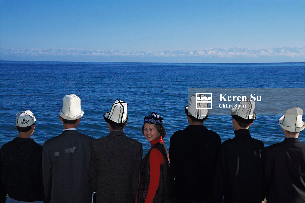 Kyrgyz girl with men wearing traditional hat with Lake Issyk-kul at back, Kyrgyzstan