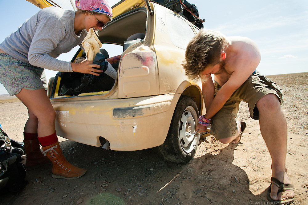 Bones Latham sorts through her car's trunk while Michael Kelly changes a flat tire in Govi-Altai Province, Mongolia.