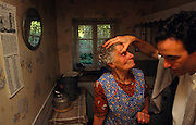 In the privacy of her own country home, an elderly French lady is about to have eye-drops administered by her local doctor in the Vosges town of Ban de Laveline. Holding her eyelids up with a thumb in preparation of giving the woman the necessary medicine, the young health professional reaches for his equipment and the lady is left looking rather startled and uncomfortable for a few moments as her eye stares wildly. We are in her small cottage on the outskirts of town and the doctor is making his rounds to various patients unable to attend his daily surgery. The lady wears a colourful apron, typical of French working people, and is possibly in her seventies, living alone with only kind neighbours to ensure her safety. ....http://www.france-voyage.com/en/