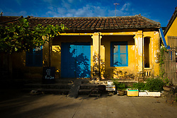 frontage of an old french colonial style house in Hoi An, Vietnam, Asia 2012. the old villa presents colorful yellow walls and blue shutters.