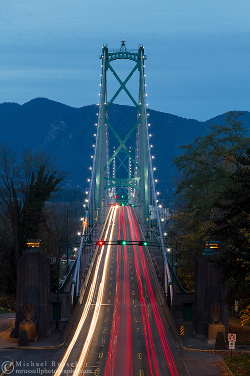 Rush hour traffic crosses the Lions Gate Bridge from Stanley Park in Vancouver, British Columbia, Canada to North Vancouver in the early evening. Photographed from the bridge on Stanley Park Drive.
