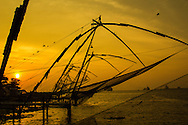 Kochi Fishing Nets Sunset - The Chinese fishing nets at  Kochi are used for a unique method of fishing. Operated from shore the nets are extended on bamboo poles and held up by huge mechanical strctures which are lowered and raised from the sea. They are counter weighed by large stones.  Each net is operated by a team of some five or six fishermen.  The net is left in the water for only a short time; just a few minutes before it is raised back up by tugging ropes. The Chinese Fishing Nets of Cochin are said to have their origin in China.