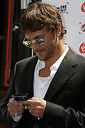 Kevin Federline, husband of the famous singer Britney Spears, is using his Virgin mobile phone moments before signing a petition in collaboration with Virgin, during a Virgin Mobile promotion event at Time Square, New York, on Wednesday, June 21, 2006. The petition against the abolition of the Penny coin, sponsored by Virgin Mobile, will be then sent over to lawyers in Washington. After this extraordinary event, Virgin Mobile will allow customers to buy 1000 text messages a month for only $9.99, just one humble penny per text.  **ITALY OUT**