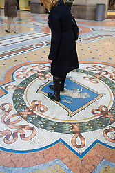 A woman rubs her heel for good luck on the crest of the bull in Galleria Vittorio Emanuele II (il salotto di Milano) Milan, Italy / Italia December 6, 2007.