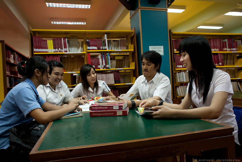 "Arttasit Tipsing (21) with fellow students in the library of Suan Dusit university. He is studying in .the Science and Technology faculty of Suan Dusit university with a major on food and service .industry. After four years of hormone treatment, he is preparing for a full sex change. ""My goal in .life is to become accepted as a woman,"" he explains..In Suan Dusit University in Bangkok, ladyboys feel free to be themselves by getting dressed in .girls' uniforms and behaving in a feminning way. The University's policy of accepting them as .equal to other students, has made it so popular that it now has about 100 transgender students .studuing in it's faculties."