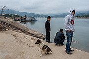 Sand dredgers try to keep warm before the day's work begins in the town of Simaogangzhen, Yunan, China. The dredged sand is sold locally and to large scale construction sites in nearby major cities such as Kunming and Jinhong.