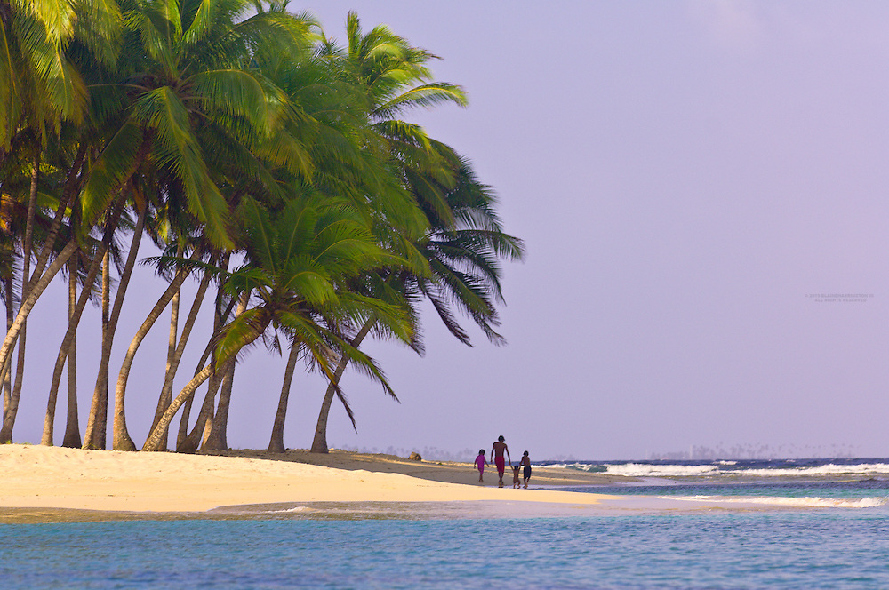 Family walking under the palm trees on Pelican Island (a.k.a. Icotupo Island), San Blas Islands (Kuna Yala), Caribbean Sea, Panama