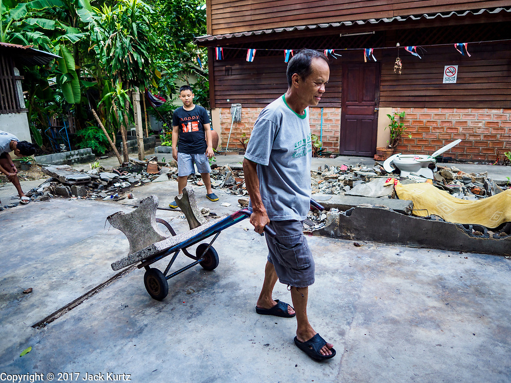 16 MAY 2017 - BANGKOK, THAILAND: A resident of Pom Mahakan moves a concrete bench in the old fort. The final evictions of the remaining families in Pom Mahakan, a slum community in a 19th century fort in Bangkok, have started. City officials are moving the residents out of the fort. NGOs and historic preservation organizations protested the city's action but city officials did not relent and started evicting the remaining families in early March.           PHOTO BY JACK KURTZ